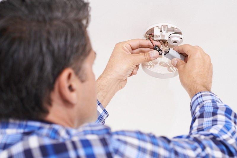 man changing battery in smoke detector