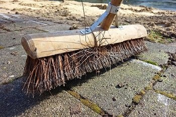 push broom sweeping up debris on concrete outside