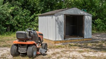 riding lawn mower outside of shed